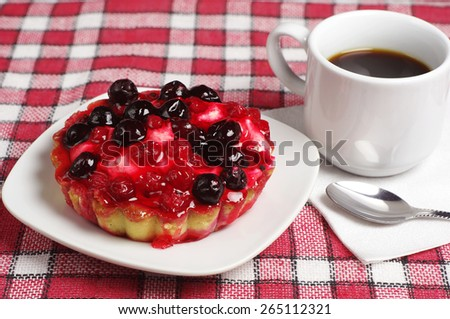 Cup of coffee and cake with currants in plate on table covert red tablecloth