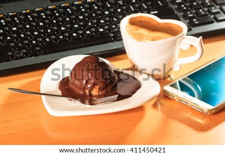 Cup of coffee and chocolate cake on heart shaped plate saucer next to laptop notebook computer keyboard and smartphone. Office work desk. - stock photo