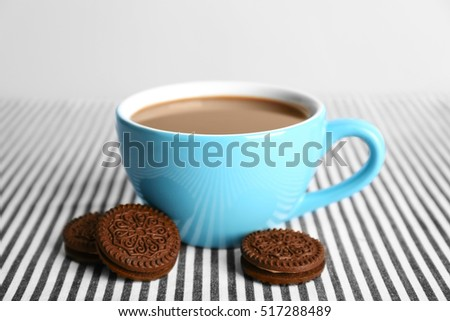 Cup of coffee and chocolate cookies with cream on table