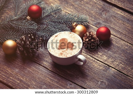 Cup of coffee and christmas toys on wooden table. - stock photo