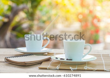 cup of coffee and coffee bean on wood table