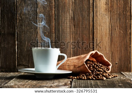 Cup of coffee and coffee beans in bag on wooden table - stock photo
