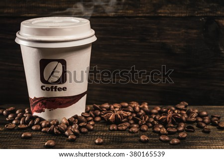 Cup of coffee and coffee beans on old wooden background - stock photo
