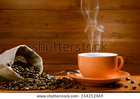 Cup of coffee and coffee beans on wooden background - stock photo