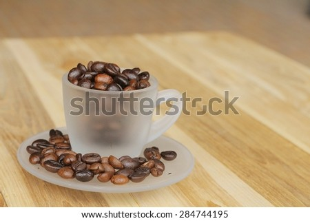 Cup of coffee and coffee beans on wooden background, Vintage style