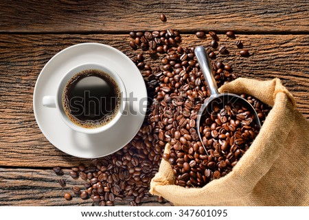 Cup of coffee and coffee beans on wooden table - stock photo