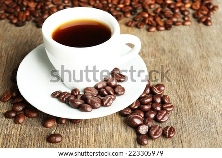 Cup of coffee and coffee beans with chocolate glaze on wooden background - stock photo