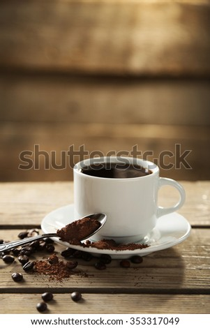 Cup of coffee and coffee grains on wooden background - stock photo