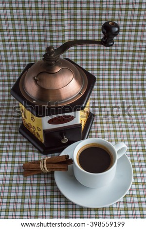 Cup of coffee and coffee mill on a light background with cinnamon - stock photo