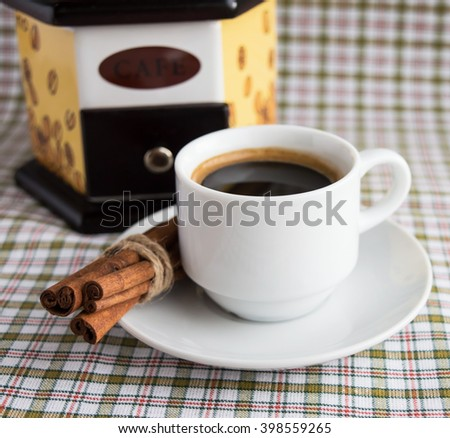 Cup of coffee and coffee mill on a light background with cinnamon. Close-up - stock photo