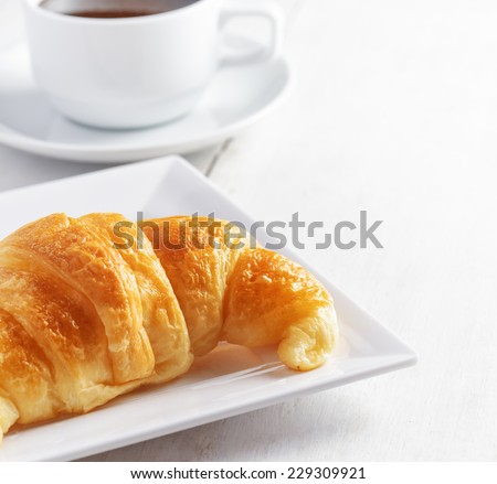 Cup of coffee and croissant on white wooden table. - stock photo