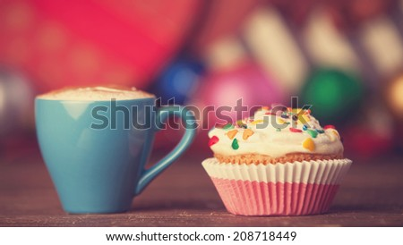 Cup of coffee and cupcake on christmas background. - stock photo