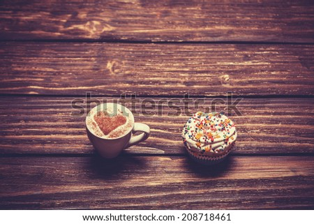 Cup of coffee and cupcake on wooden table. - stock photo