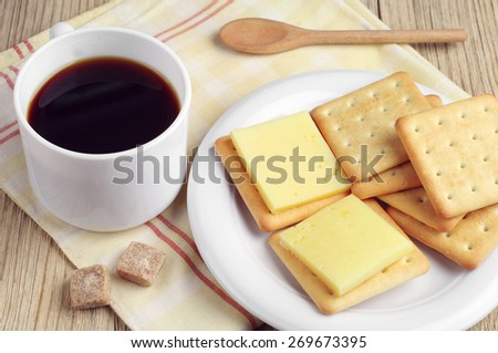 Cup of coffee and delicious cracker cookies with cheese and on table - stock photo