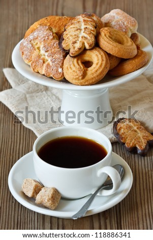 Cup of coffee and delicious homemade cookie on a cake stand.