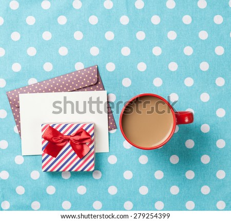 Cup of coffee and envelope with gift boxes on blue polka dot background  - stock photo