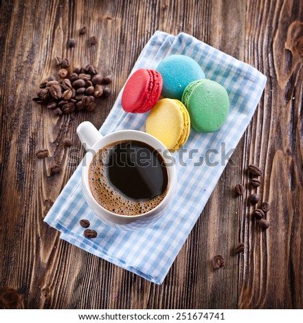 Cup of coffee and french macaron on an old wooden table. - stock photo