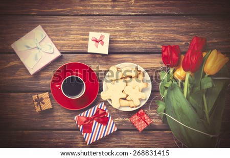 Cup of coffee and gift around with flowers on wooden table. Photo in old color image style