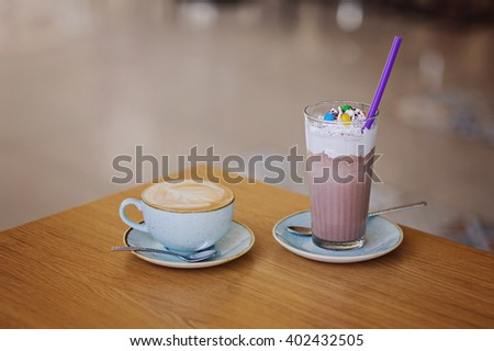 Cup of coffee and Glass of sweet cacao with chocolate and whipped cream on rustic wooden table in cafe. Top view. - stock photo