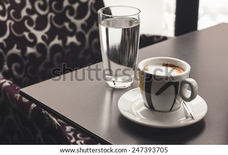 Cup of coffee and glass of water on table in a cafe.  - stock photo