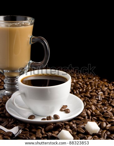 cup of coffee and glass on roasted beans as background isolated on black background - stock photo