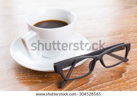 cup of coffee and glasses on wooden table