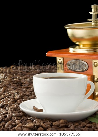 cup of coffee and grinder isolated on black background - stock photo
