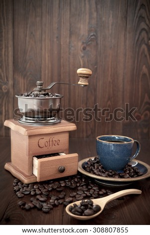 Cup of coffee and grinder on wooden background