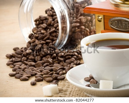 cup of coffee and grinder with roasted beans - stock photo