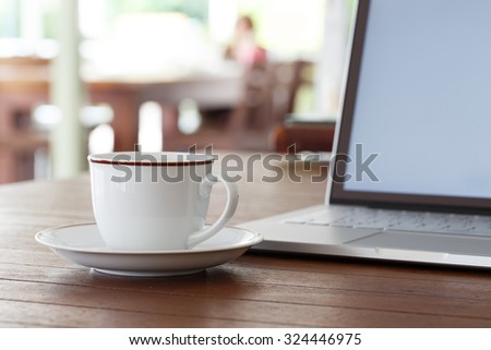 Cup of coffee and laptop computer on wooden table