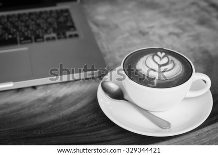 Cup of coffee and laptop computer on wooden table, warm retro style. - stock photo