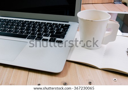 cup of coffee and laptop in the office put on the wood texture background