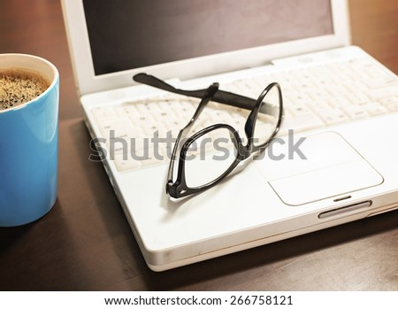 Cup of coffee and laptop with a pair of hipster glasses on wooden table  - stock photo