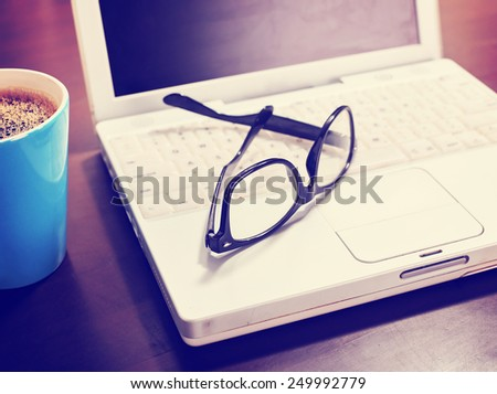 Cup of coffee and laptop with a pair of hipster glasses on wooden table toned with a retro vintage instagram filter - stock photo