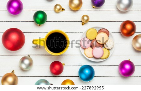 Cup of coffee and macaron with christmas toys on whte background. - stock photo
