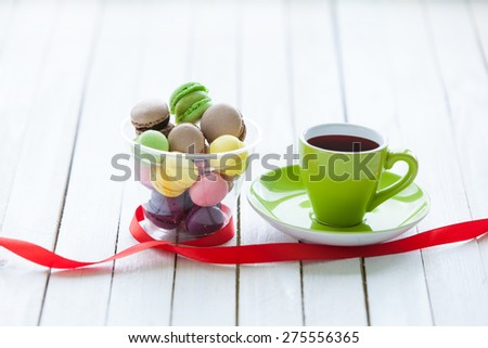 Cup of coffee and macarons near ribbon on wooden table.