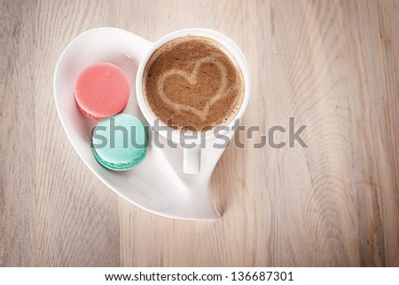 cup of coffee and macaroons in a heart shaped porcelain on wooden table - stock photo