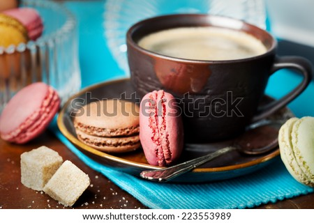 Cup of coffee and macaroons on wooden table, toned  - stock photo