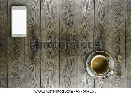 cup of coffee and mobile phone on wood table. - stock photo
