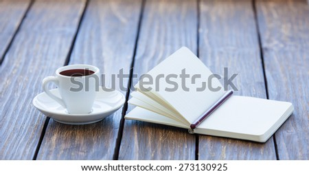 Cup of coffee and notebook with pencil on wooden table. - stock photo
