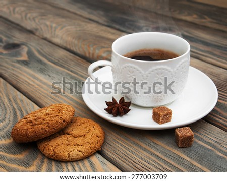 Cup of coffee and oatmeal cookies on a wooden background - stock photo