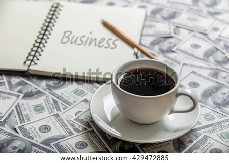 """Cup of coffee and open book with word """"business"""", focus a cup - stock photo"""