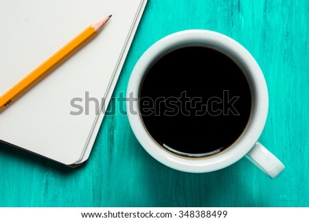 Cup of coffee and paper notebook with pencil
