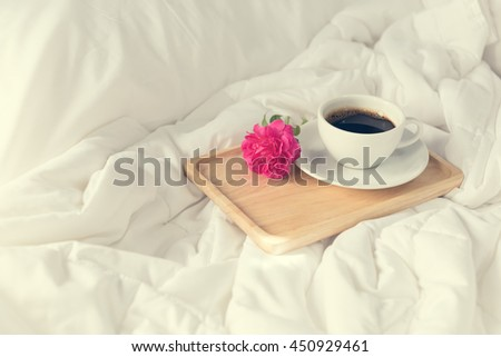 Cup of coffee and pink rose flower with wooden tray on bed background