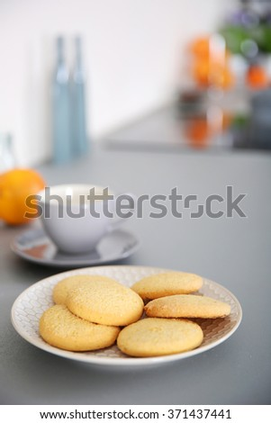 Cup of coffee and plate of cookies on the table against unfocused background - stock photo