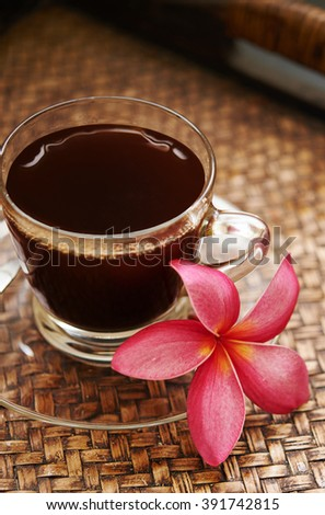 cup of coffee and plumeria flower in otrental style - stock photo