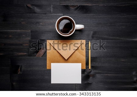 Cup of coffee and postal envelope with card on the wood desk, top view at the studio - stock photo