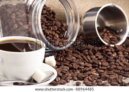cup of coffee and pot with roasted beans with sack burlap - stock photo
