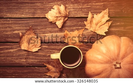 Cup of coffee and pumpkin with leafs on wooden table - stock photo