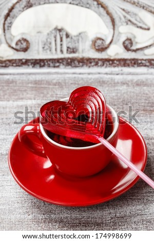 Cup of coffee and red lollipop in heart shape  - stock photo